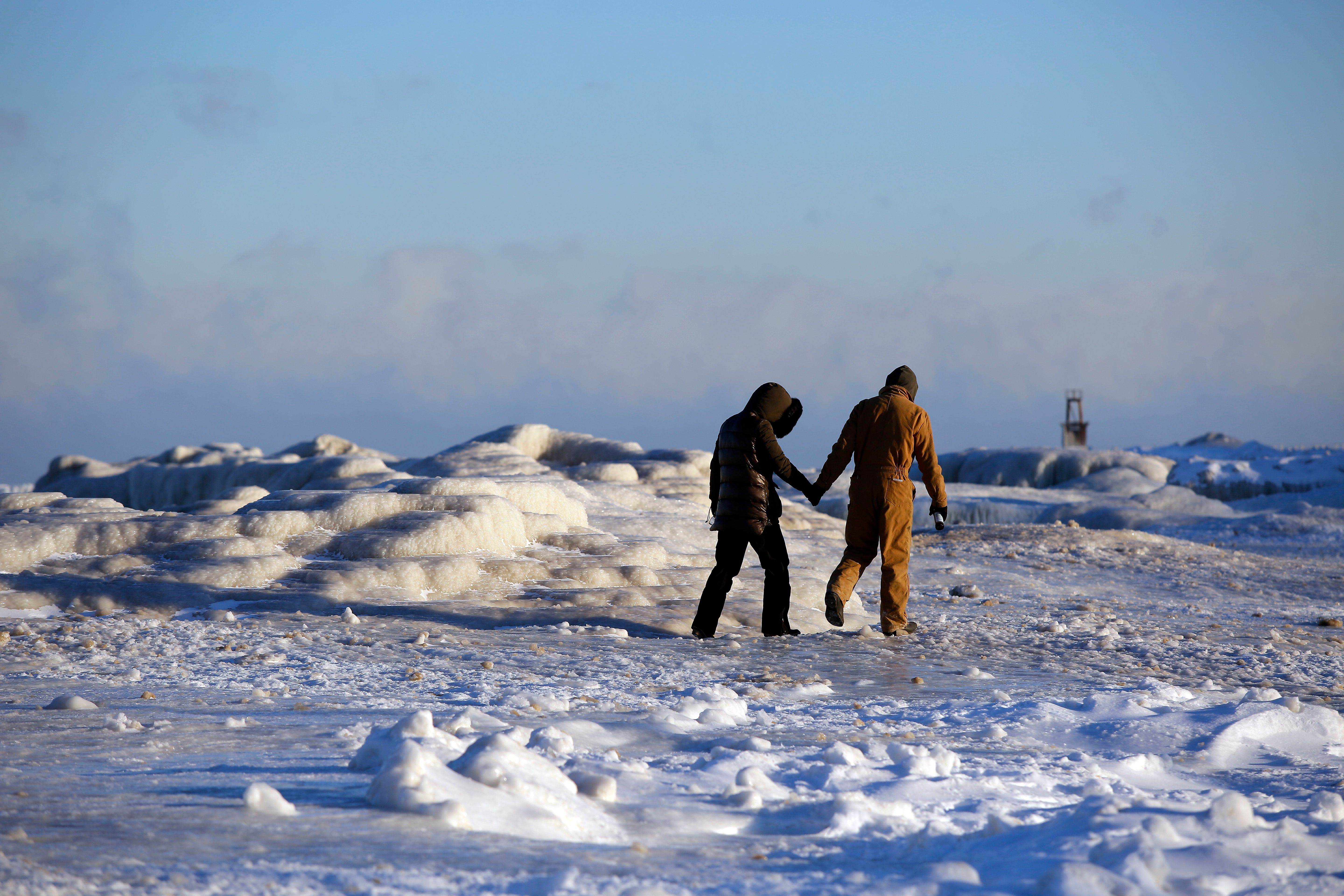 Frank Lettiere and Jelena Miletic hold hands as they view Lake Michigan's frozen shoreline in Chicago.