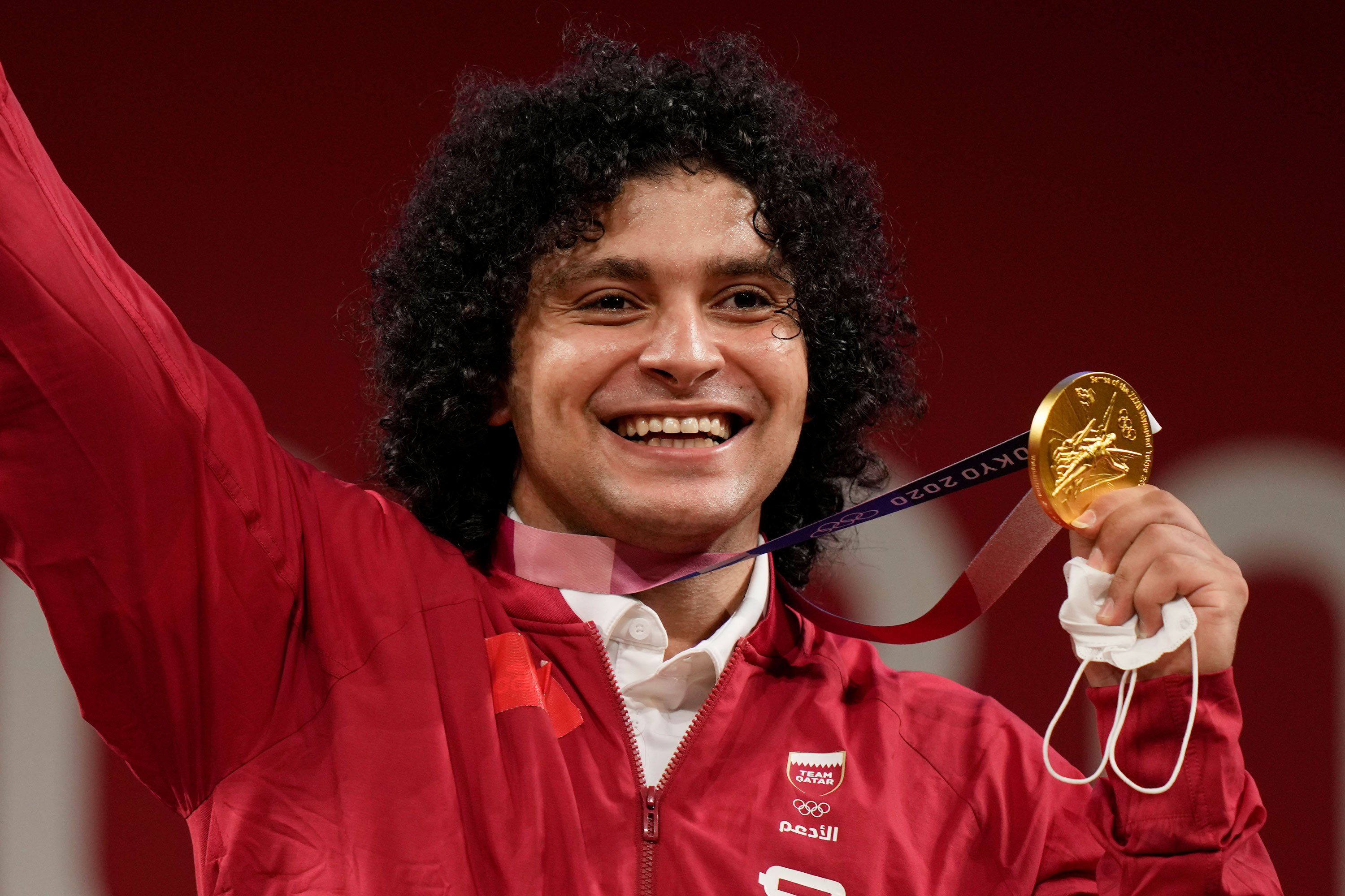 Qatar's Fares El-Bakh celebrates on the podium after winning the gold medal in the 96kg weightlifting event on July 31.