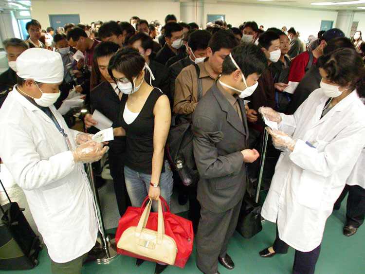 Chinese health officials check the health declarations by passengers boarding flights at the Nanjing airport on April 25, 2003.