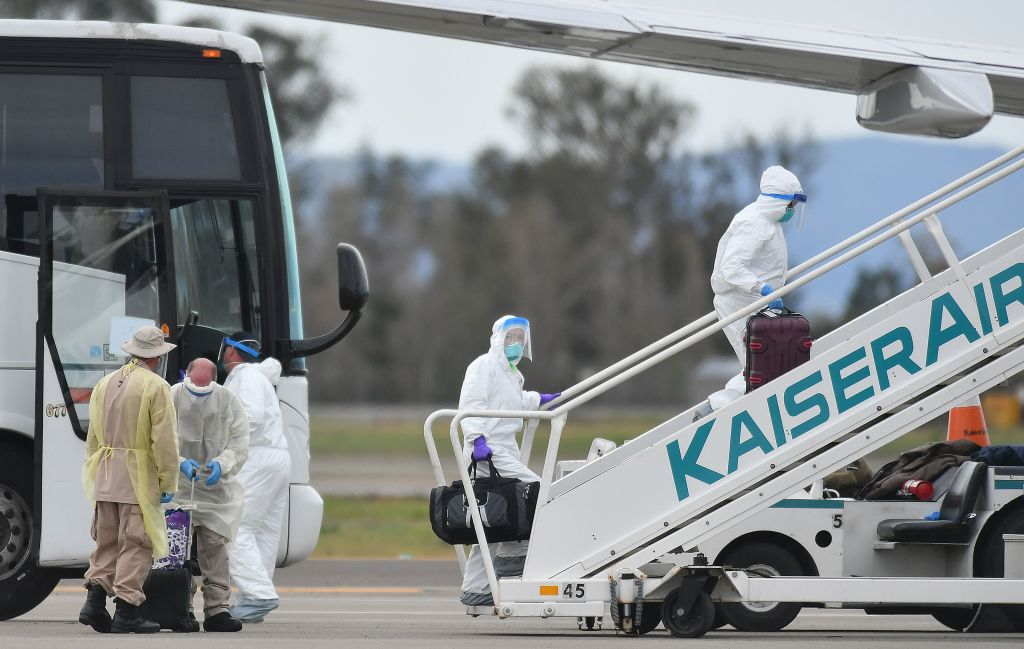 Medical personnel help load passengers from the Grand Princess cruise ship onto airplanes in Oakland, California, on Tuesday.