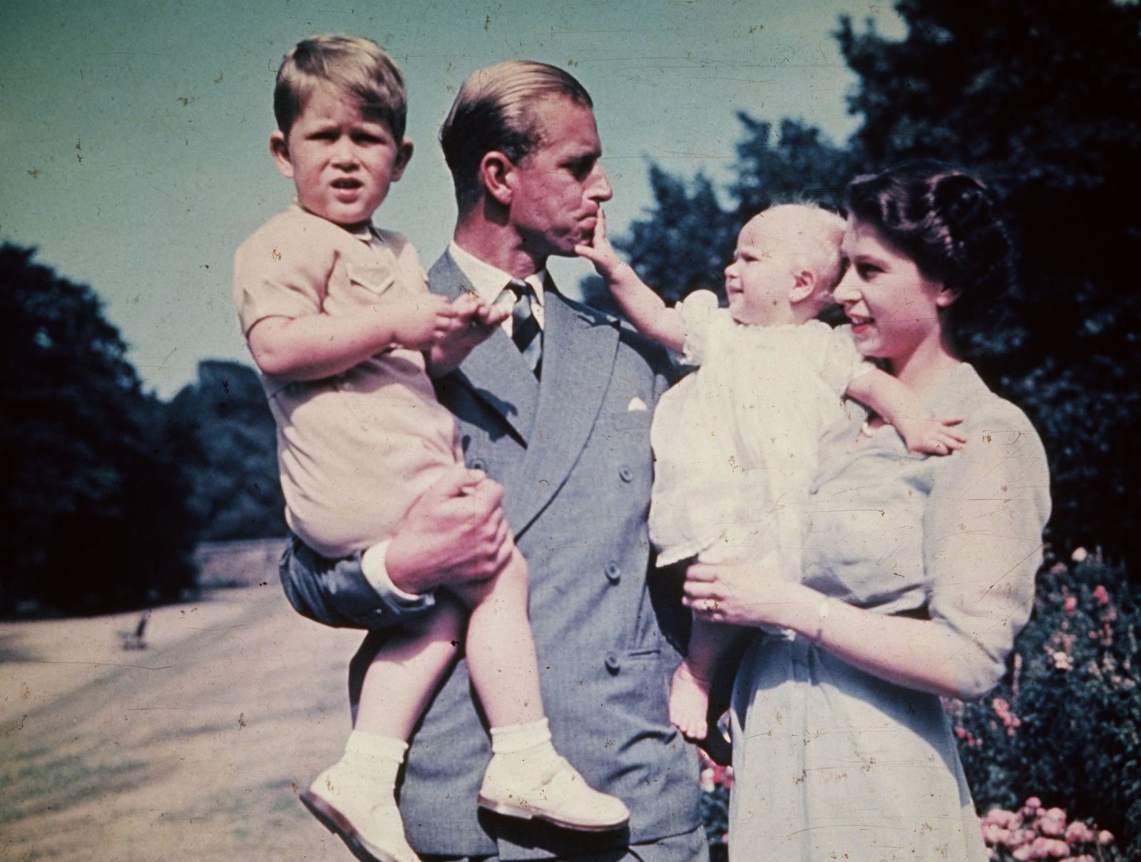 Philip and Elizabeth hold their children, Prince Charles and Princess Anne, in August 1951.
