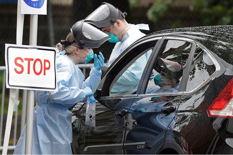 Medical workers administer tests for the coronavirus to people in vehicles, Thursday, June 11, in the Roxbury neighborhood of Boston.