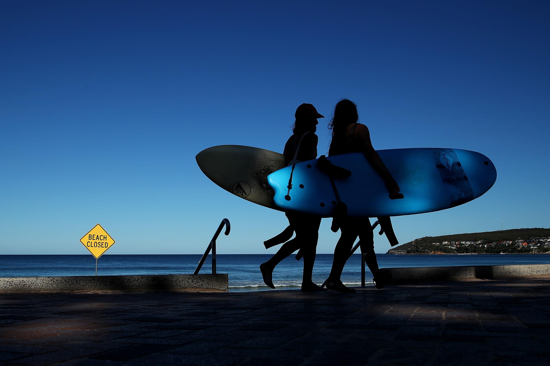 Surfers walk along Manly Beach in Sydney, Australia on April 5.