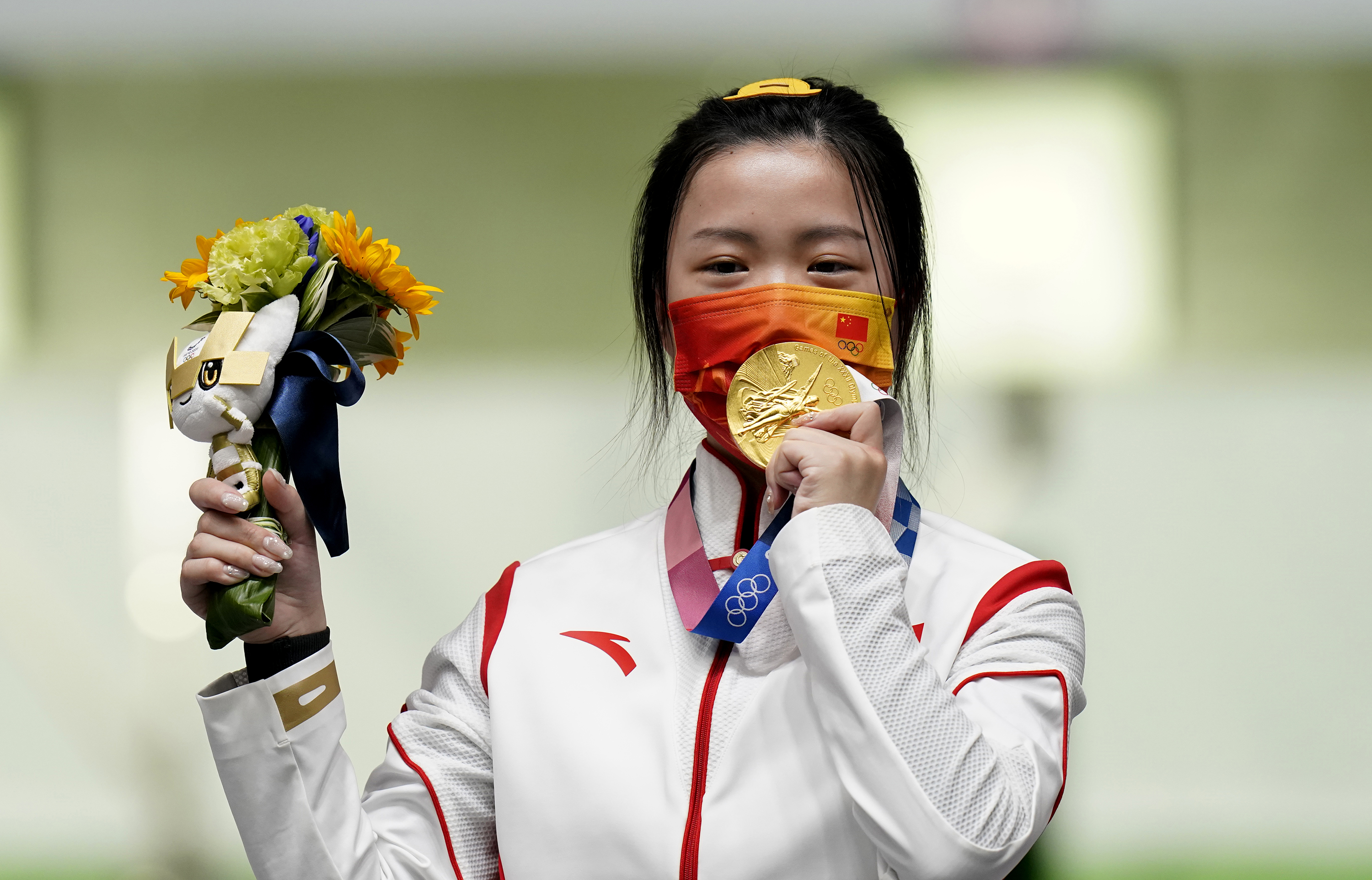 China's Yang Qian celebrates with her gold medal after winning the women's 10m air rifle on Saturday, July 24.