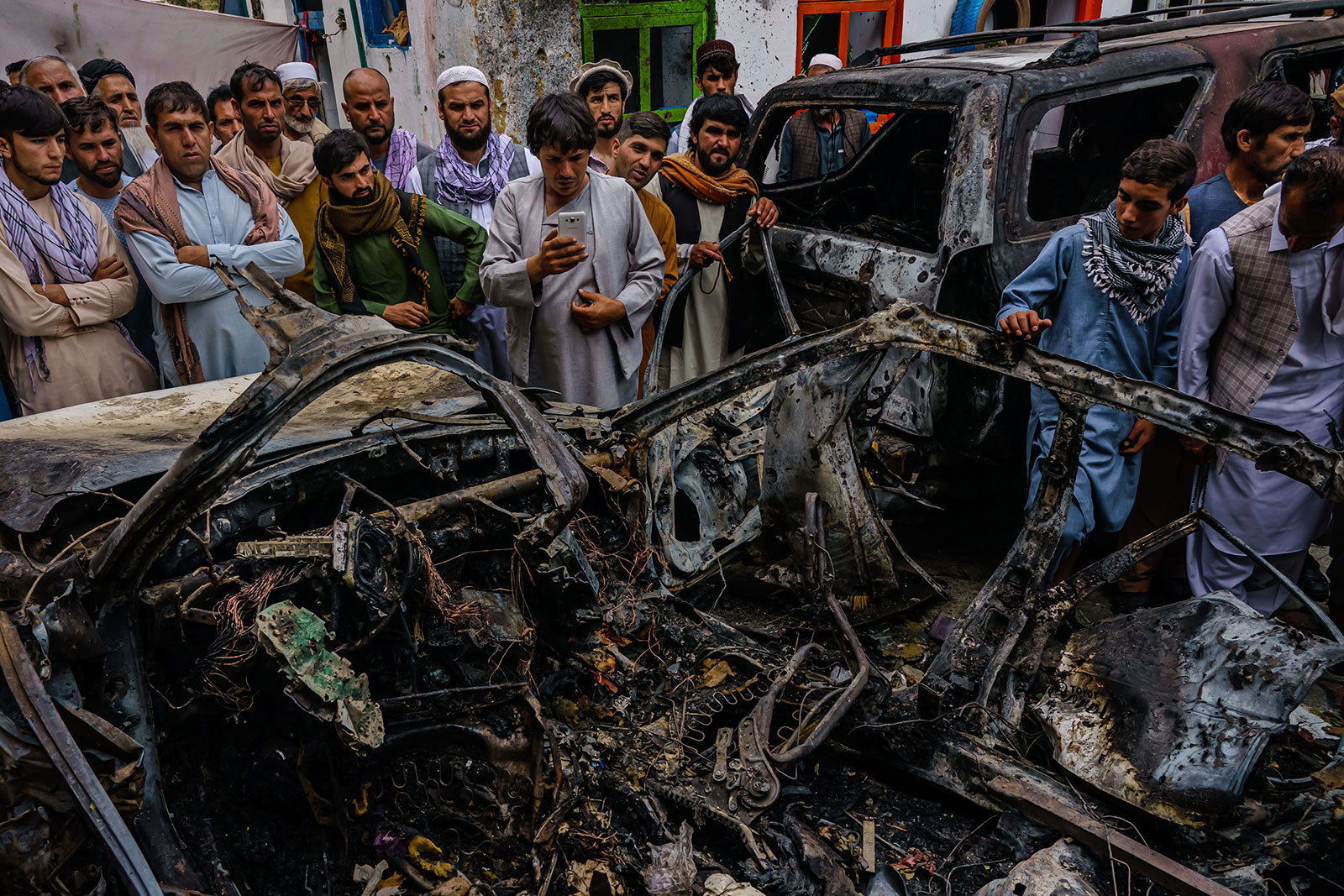 Relatives and neighbors inspect the remains of the US drone strike in a residential compound in Kabul on August 30.