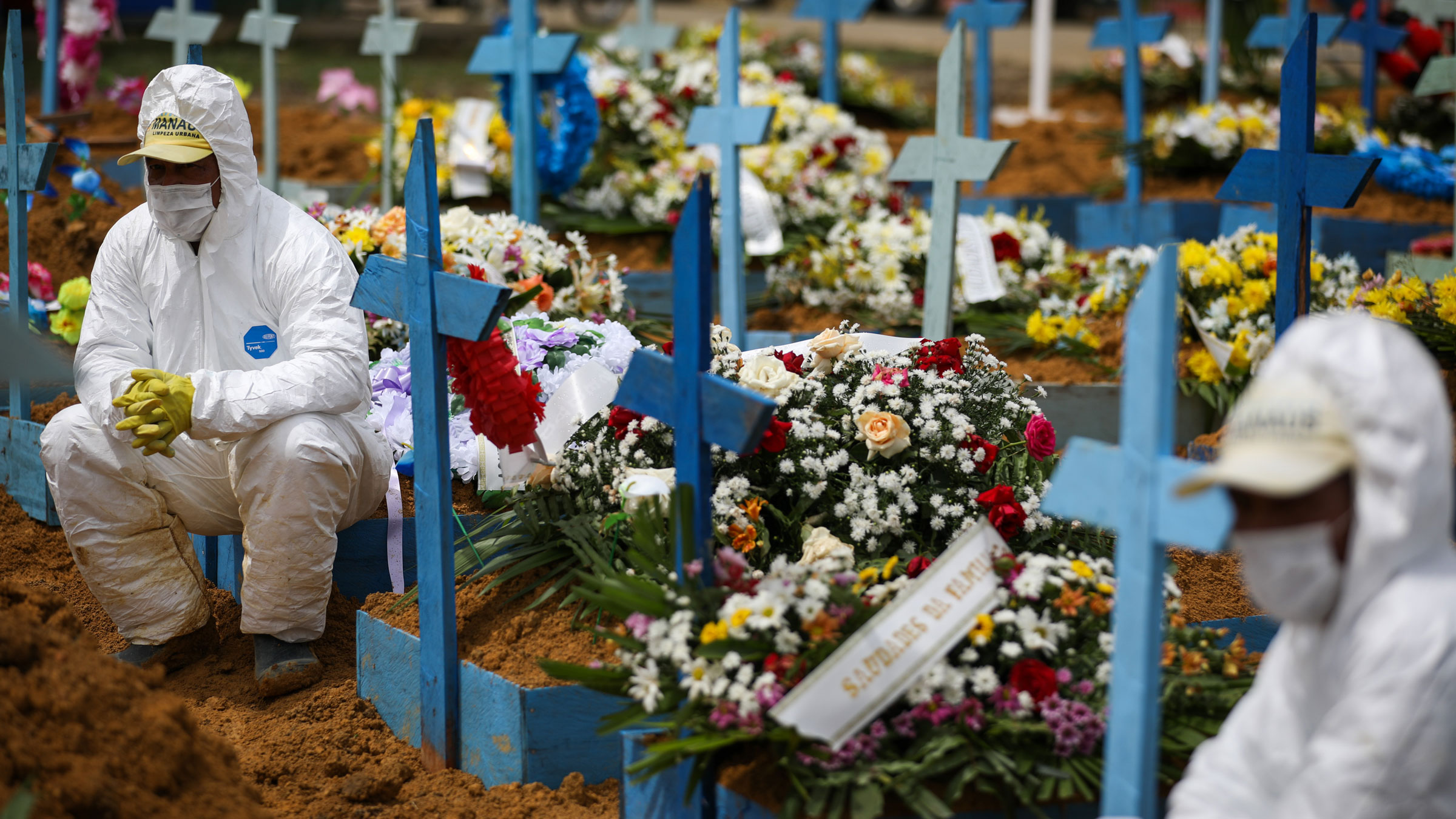 Cemetery workers sit on graves in January during a funeral at the Nossa Senhora Aparecida Cemetery in Manaus, Brazil.