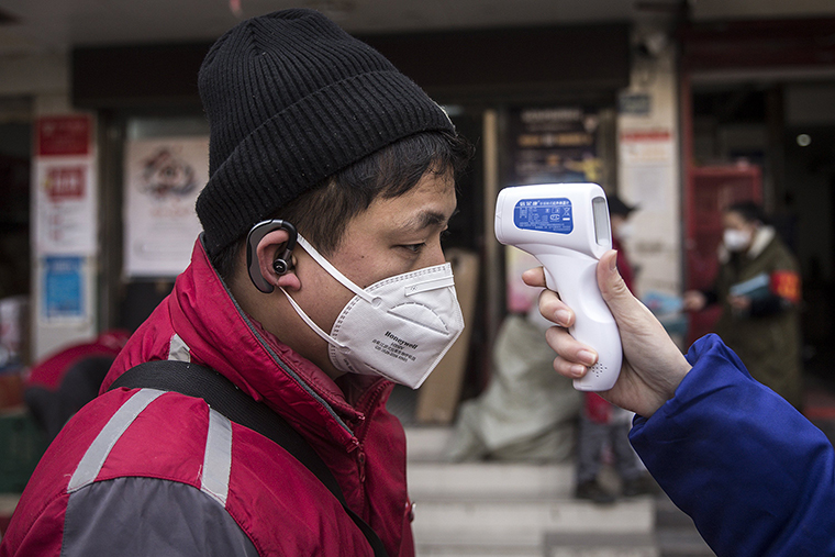 A community worker checks the temperature of courier in an Express station on Wednesday, January 29, in Wuhan, China.