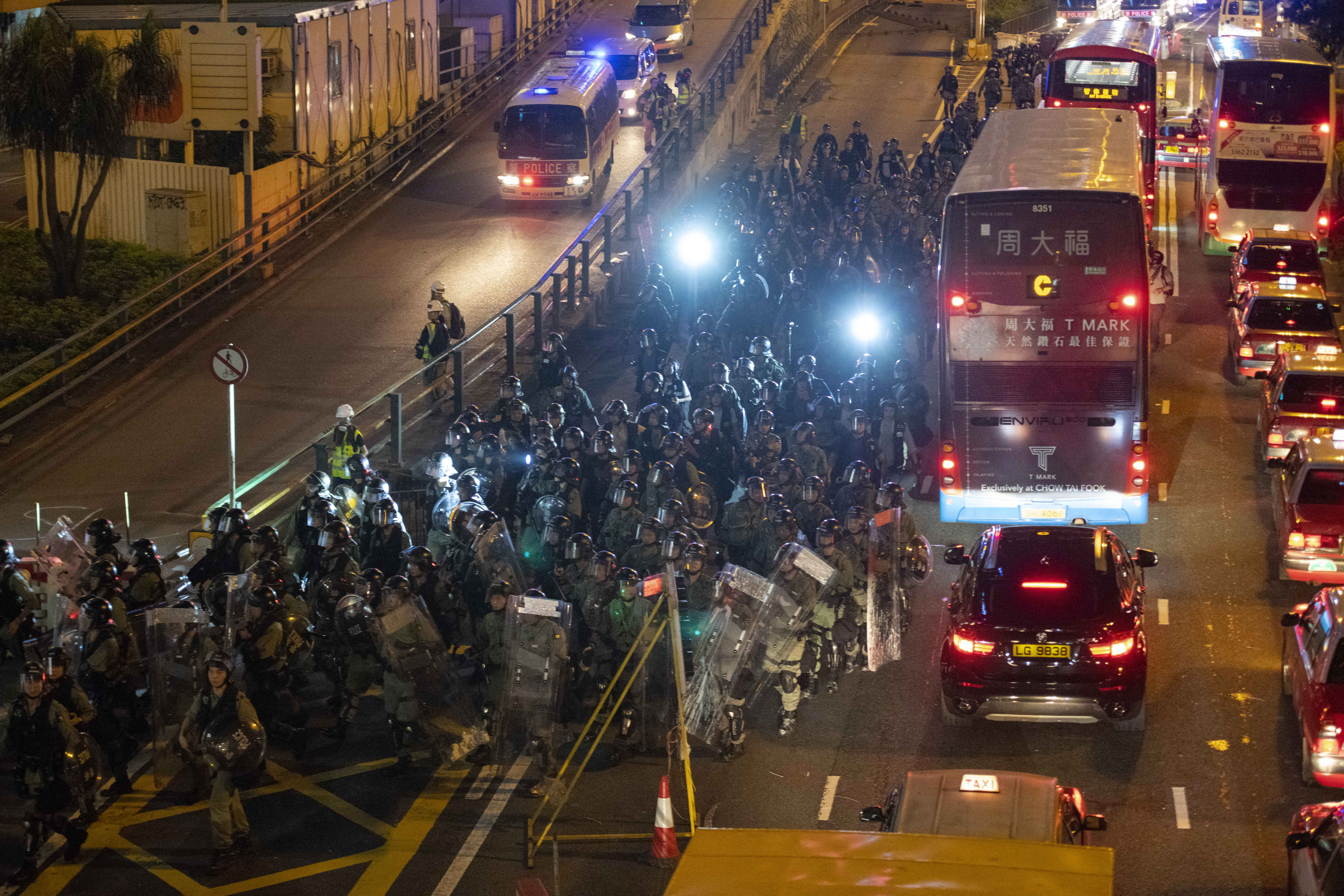 Riot police follow protesters into Causeway Bay from Gloucester Road Sunday night.