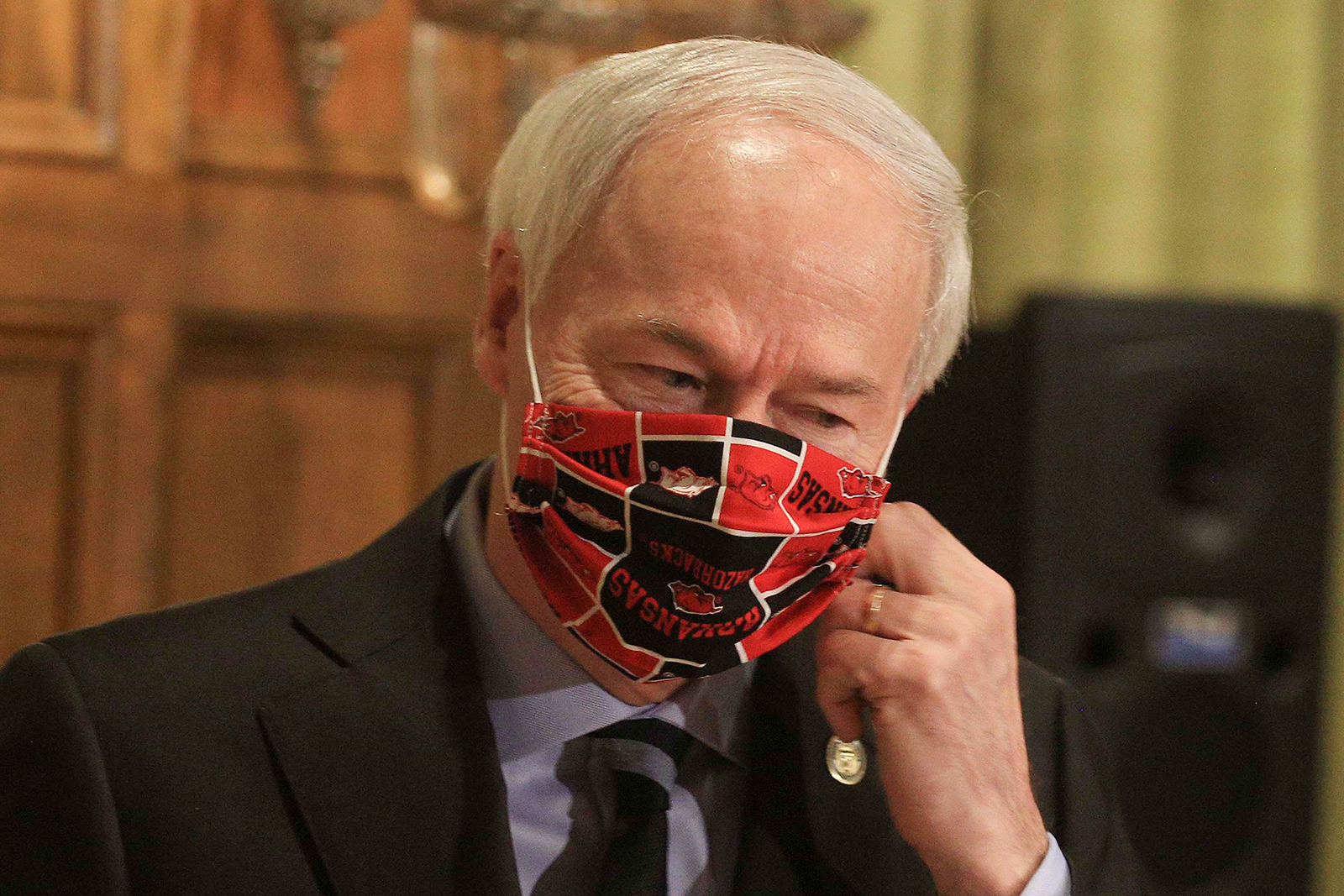 Gov. Asa Hutchinson takes off his Arkansas Razorbacks facemark as he arrives for the daily coronavirus briefing at the state Capitol in Little Rock on April 27.