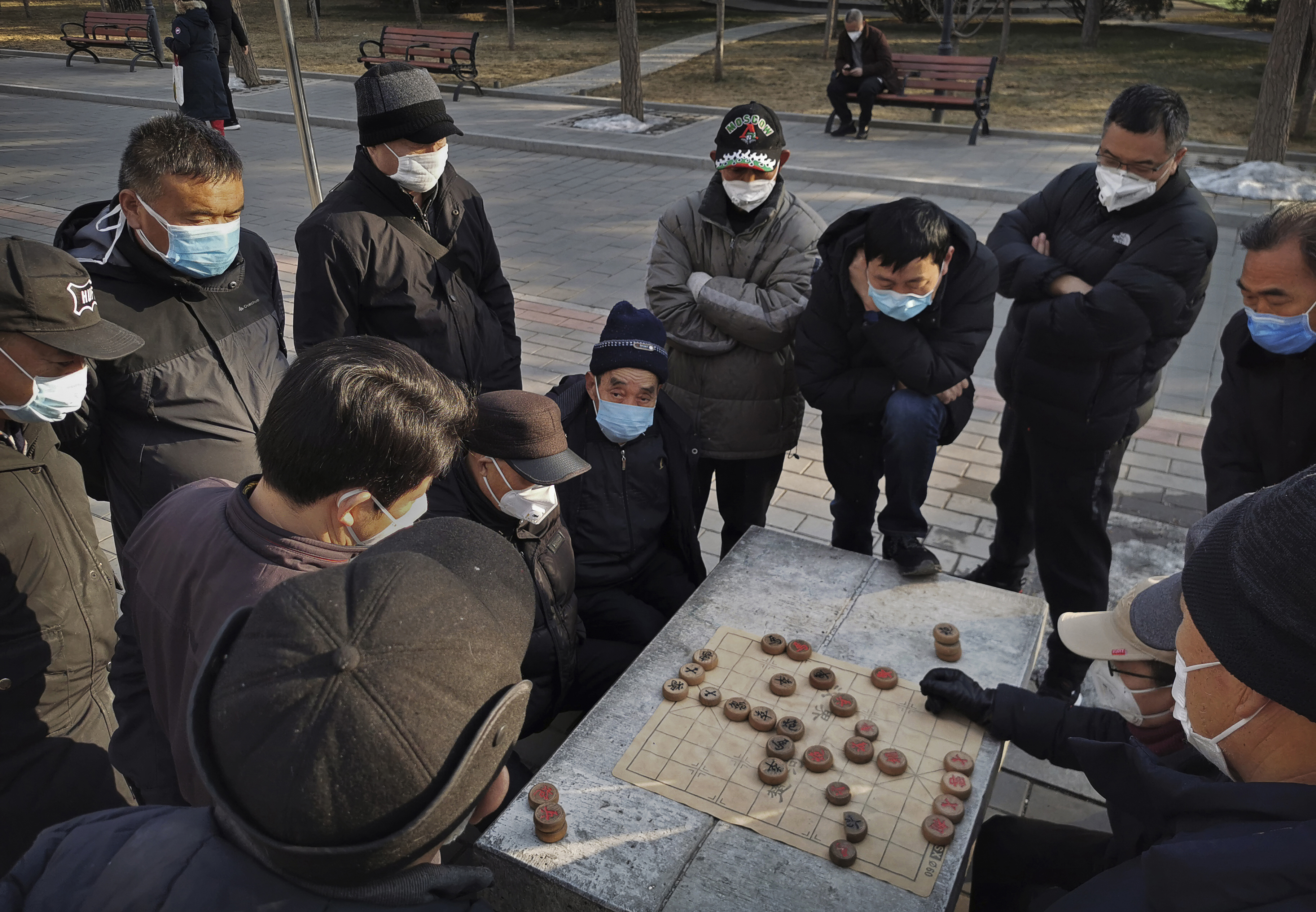 Men wear masks as they play Chinese chess in a Beijing park on January 31, 2020.
