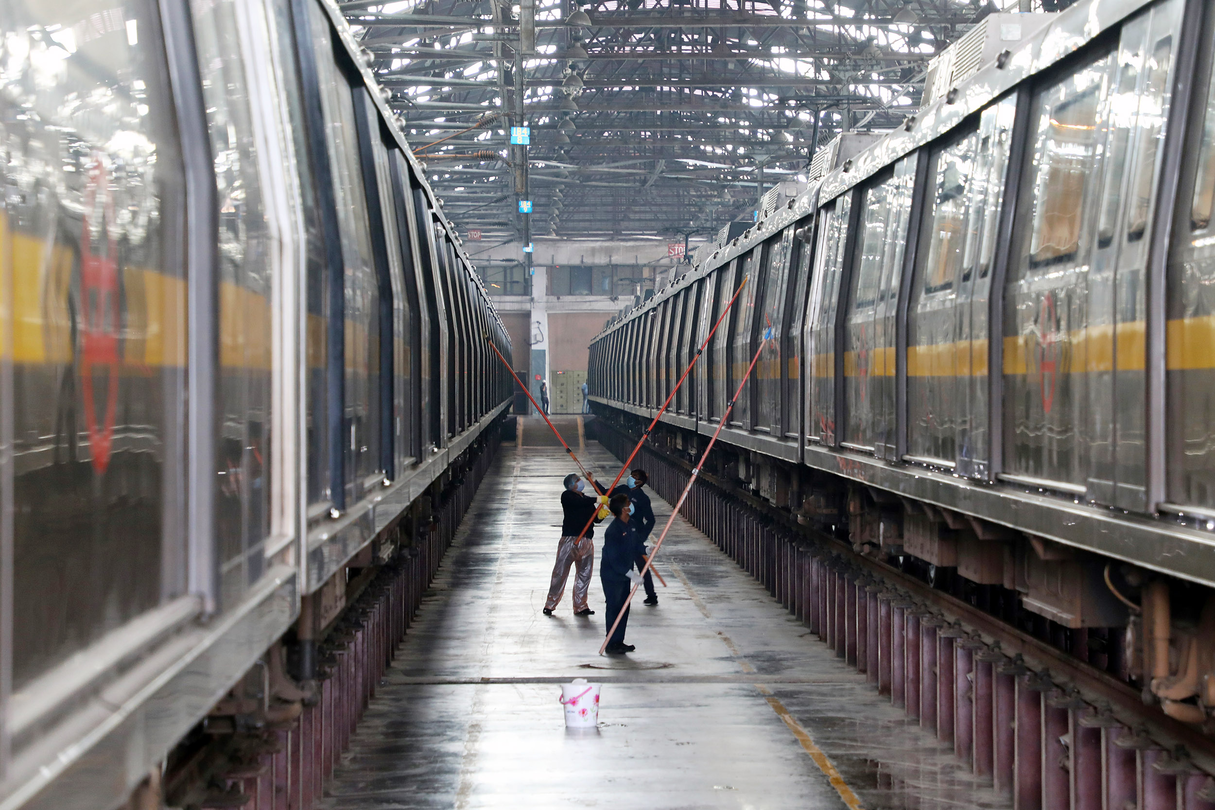 Workers disinfect the exterior a Delhi metro rail carriage.