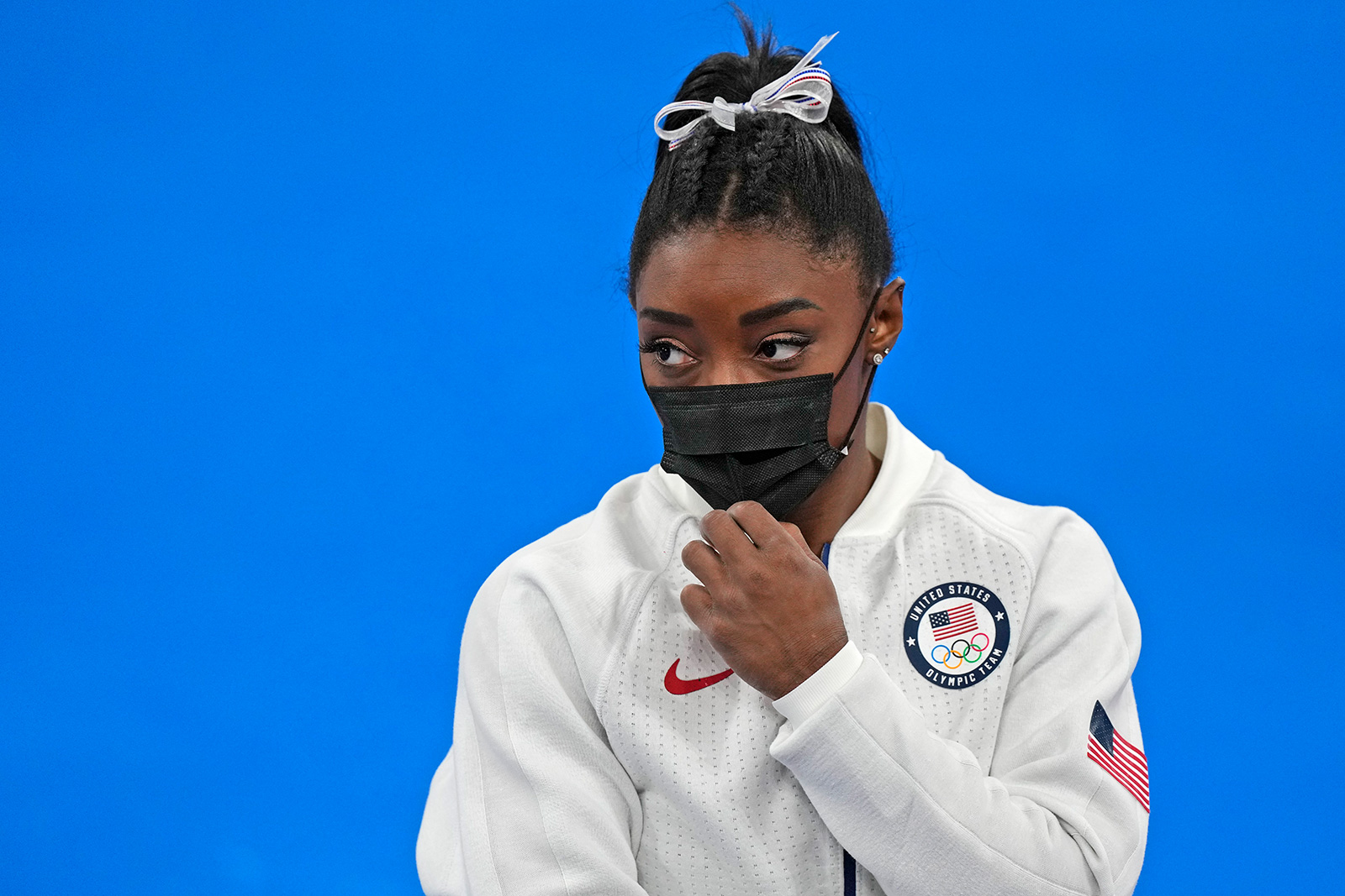 American gymnast Simone Biles stands wearing a mask after she exited the team gymnastics final on July 27.