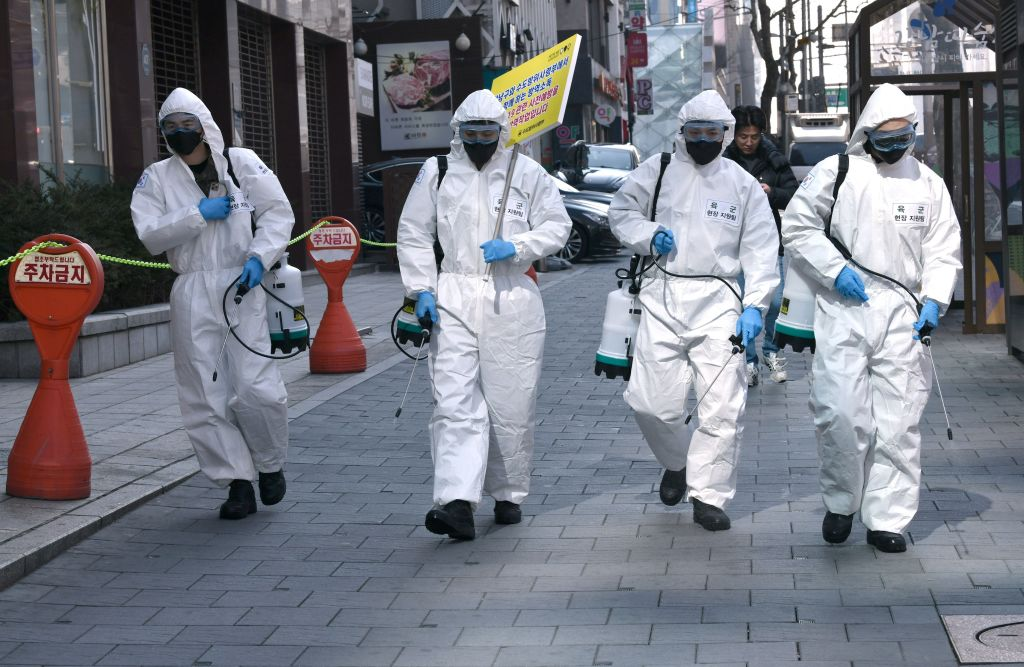 South Korean soldiers wearing protective gear spray disinfectant on the street to help prevent the spread of the coronavirus in Seoul today.