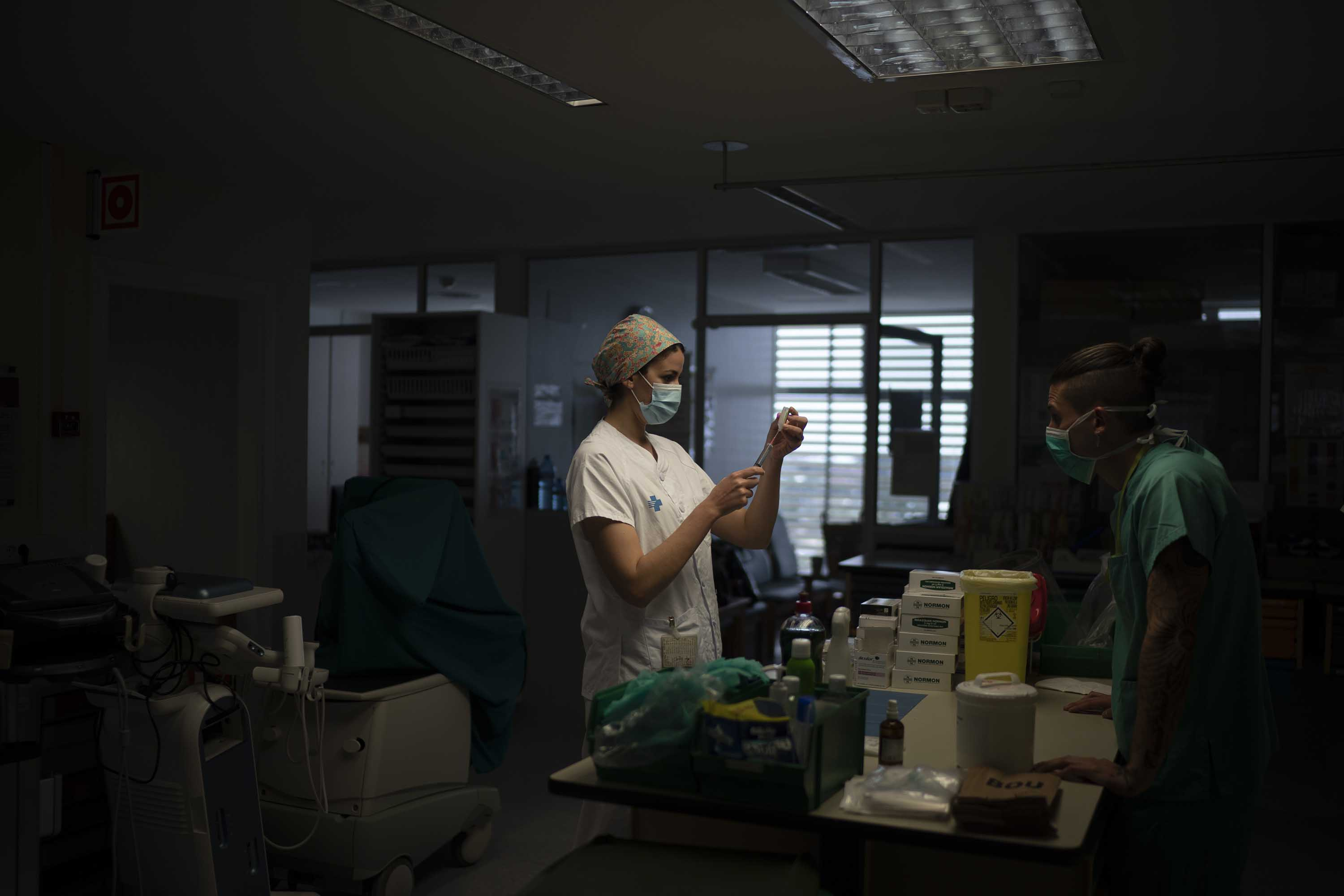 A healthcare worker prepares medication for a coronavirus patient at a hospital in Badalona, Spain, on April 1.
