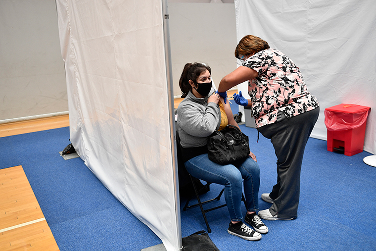 A nurse administers a dose of the Moderna Covid-19 vaccine at a clinic for Catholic school education workers including elementary school teachers and staff at a vaccination site at Loyola Marymount University on March 8,  in Los Angeles, California.