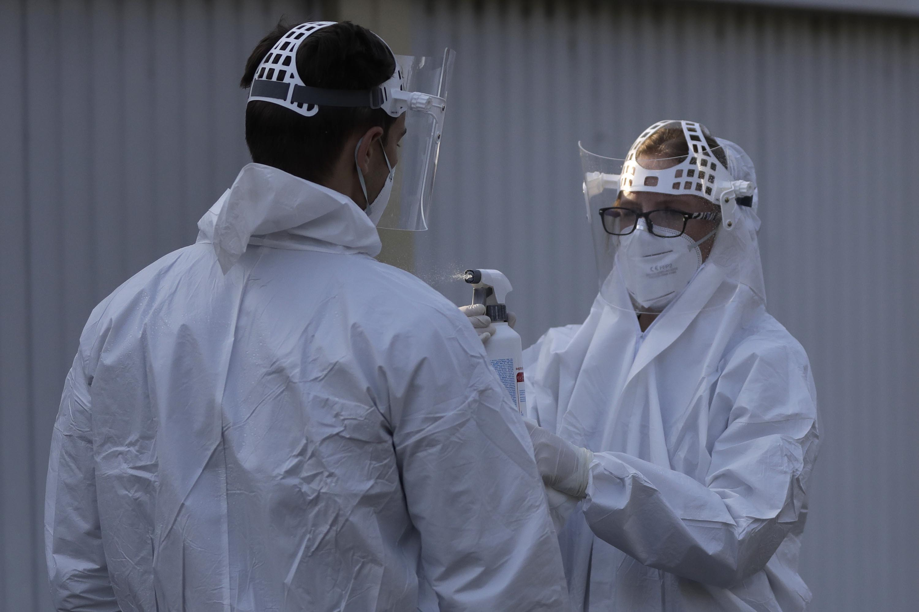 A healthcare worker has his protective suit disinfected by another worker at a COVID-19 sampling station in Prague, Czech Republic, on September 21.