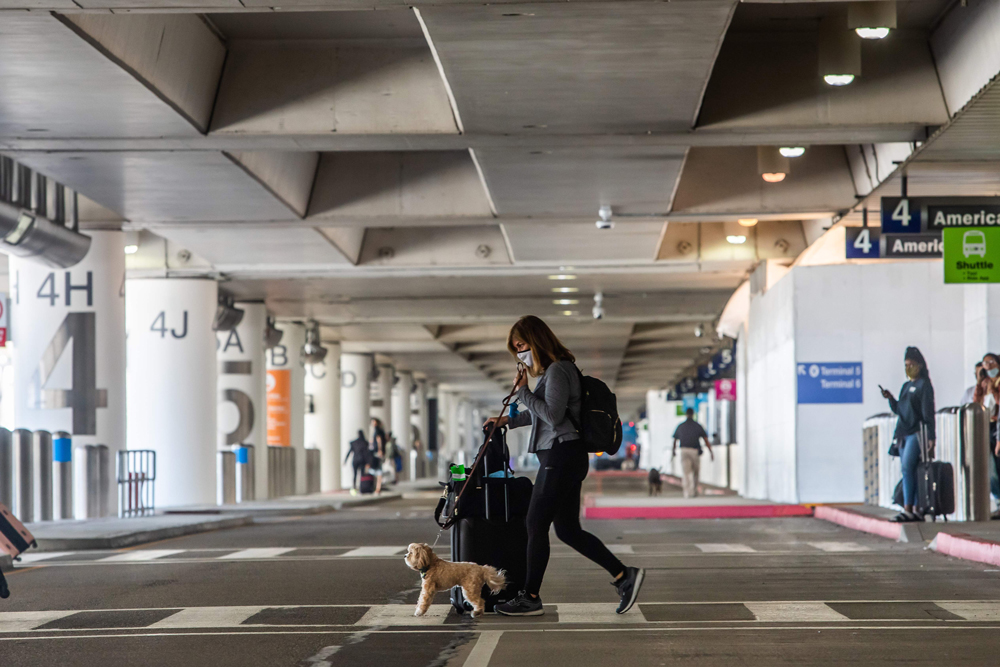 A woman crosses the street at LAX airport on May 22, in Los Angeles.