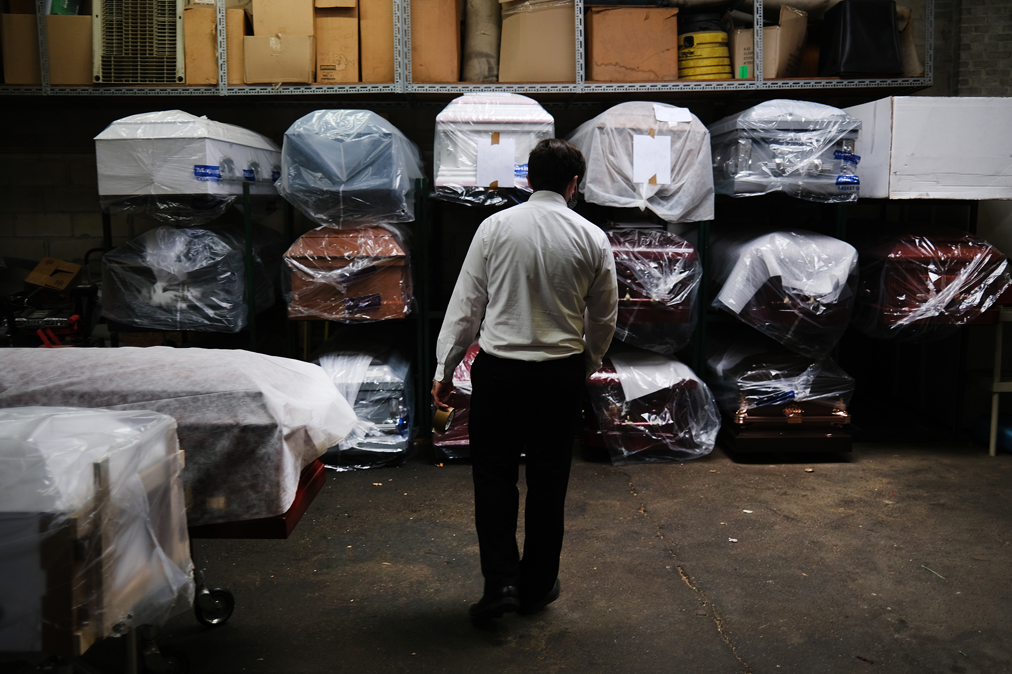 A funeral home worker tends to the inventory of pre-sold caskets at a funeral home on April 29, 2020 in New York City.