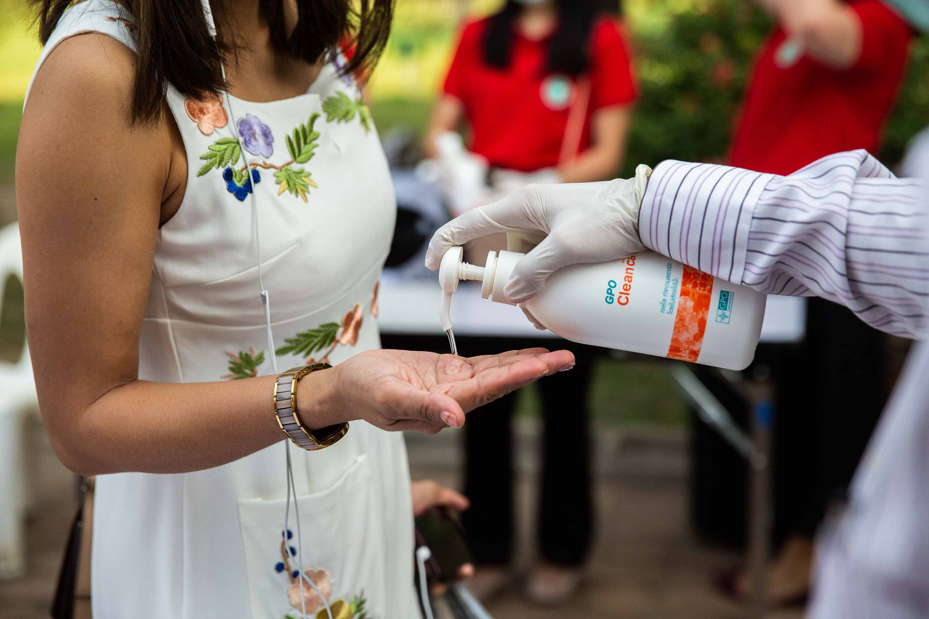 Thai people are given hand sanitizing gel before receiving a free face mask at The Ministry of Public Health in Bangkok, Thailand, on Tuesday.