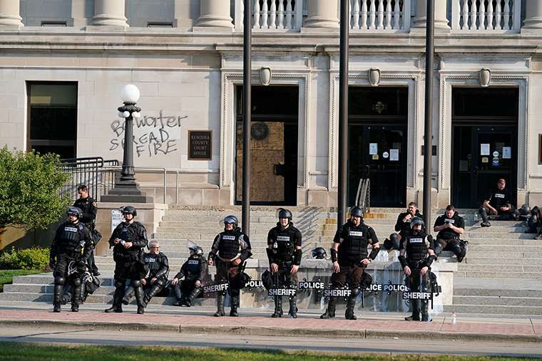 Police in riot gear stand outside the Kenosha County Court House Monday, Aug. 24, in Kenosha, Wisc. Kenosha police shot a man Sunday evening, setting off unrest in the city after a video appeared to show the officer firing several shots at close range into the man's back. (AP Photo/Morry Gash)