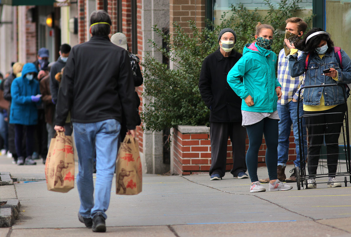 Customers wearing masks line up outside the Trader Joe's grocery store in Coolidge Corner in Brookline, MA on April 8, 2020.
