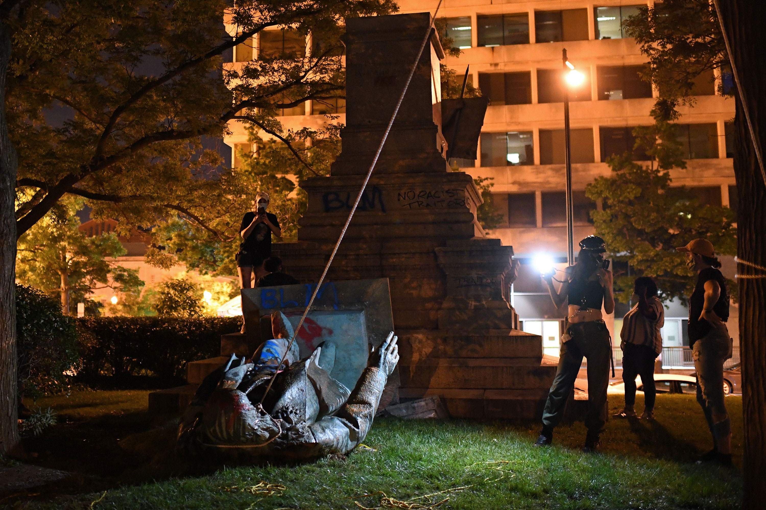 People stand around the statue of Confederate general Albert Pike after it was toppled by protesters on June 19 in Washington.