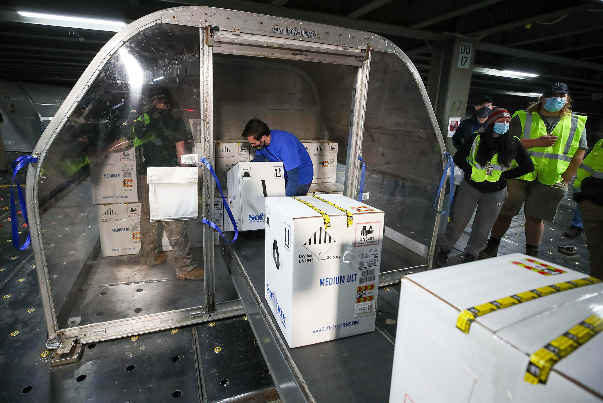 Boxes containing the first shipments of the Pfizer and BioNTech COVID-19 vaccine are unloaded from air shipping containers at UPS Worldport on December 13 in Louisville, Kentucky.