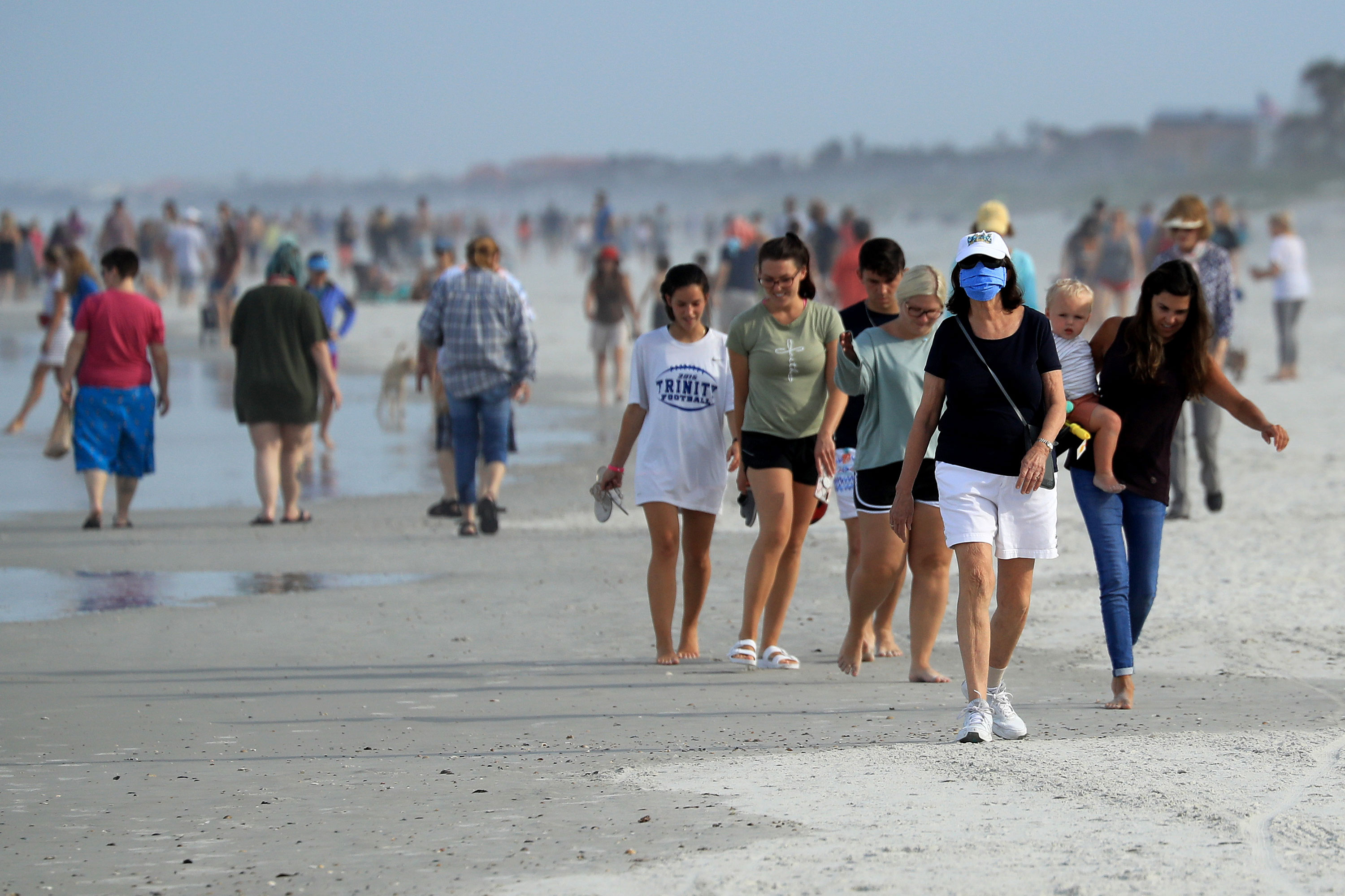 People walk down the beach on April 19 in Jacksonville Beach, Florida.