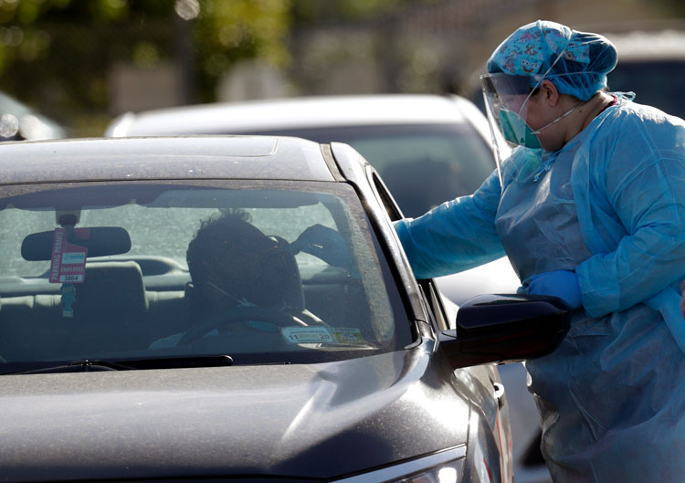 A man is swabbed as he is tested for Covid-19 as vehicles line up at the Doris Ison Health Center, Wednesday, March 18, in Miami.