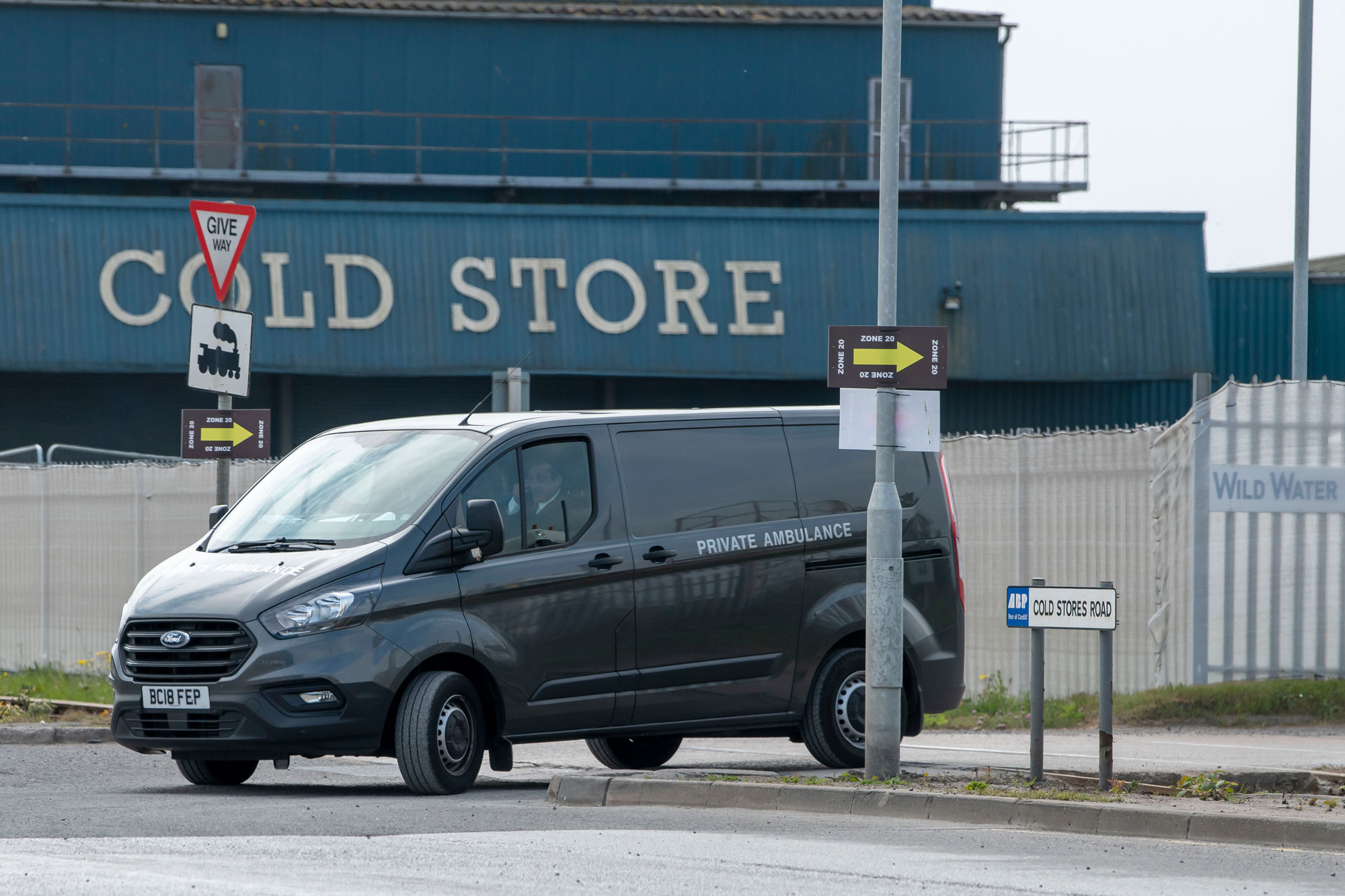 A vehicle marked 'Private Ambulance' leaves the Wild Water Group cold storage warehouse, the site of a temporary mortuary facility, on April 26, in Cardiff, United Kingdom.