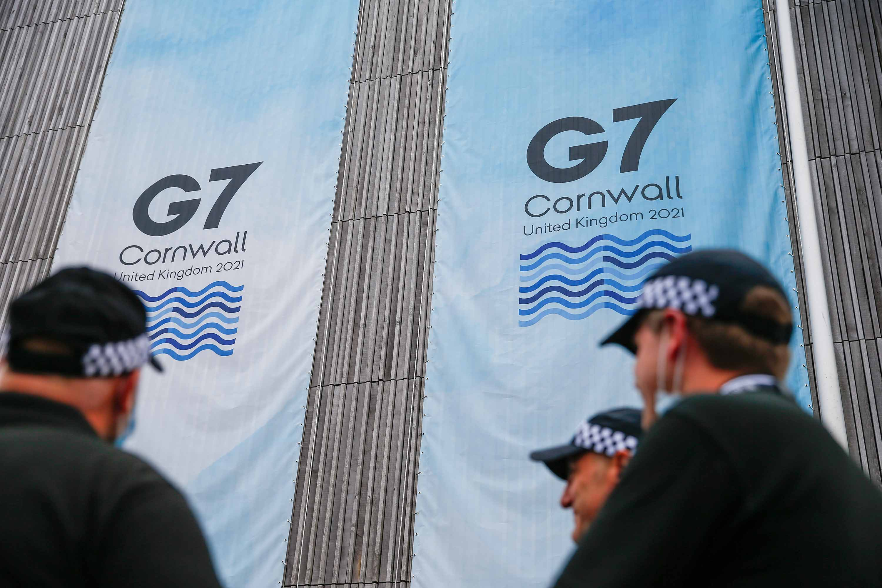 Police officers stand near a sign outside the media center on the first day of the G7 summit in Carbis Bay, England, on Friday, June 11.