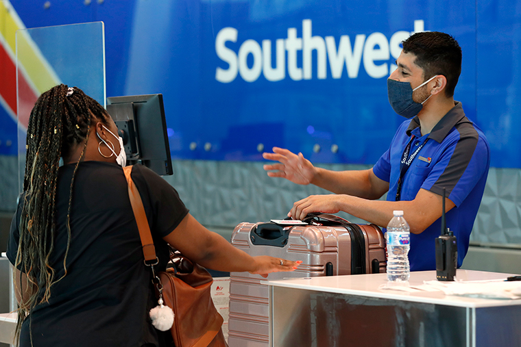 Southwest airlines employee Oscar Gonzalez, right, assists a passenger at the ticket counter at Love Field in Dallas on Wednesday, June 24.