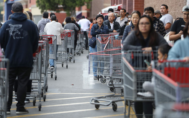 People wait in line to enter a Costco Wholesale store before it opened in the morning on March 12 in Glendale, California.