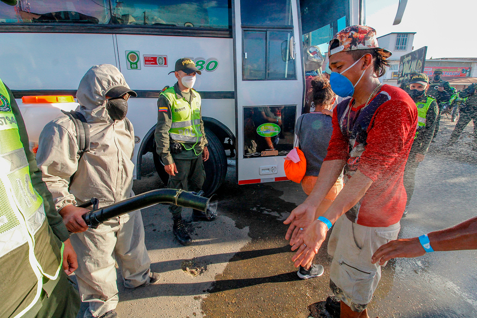 Police officers spray disinfectant on Venezuelans and their baggage as they are being transferred from the Simon Bolivar international crossing point to the Tienditas International Bridge where they will be housed in tents, in Cucuta, Colombia, on the border with Venezuela, on June 14.