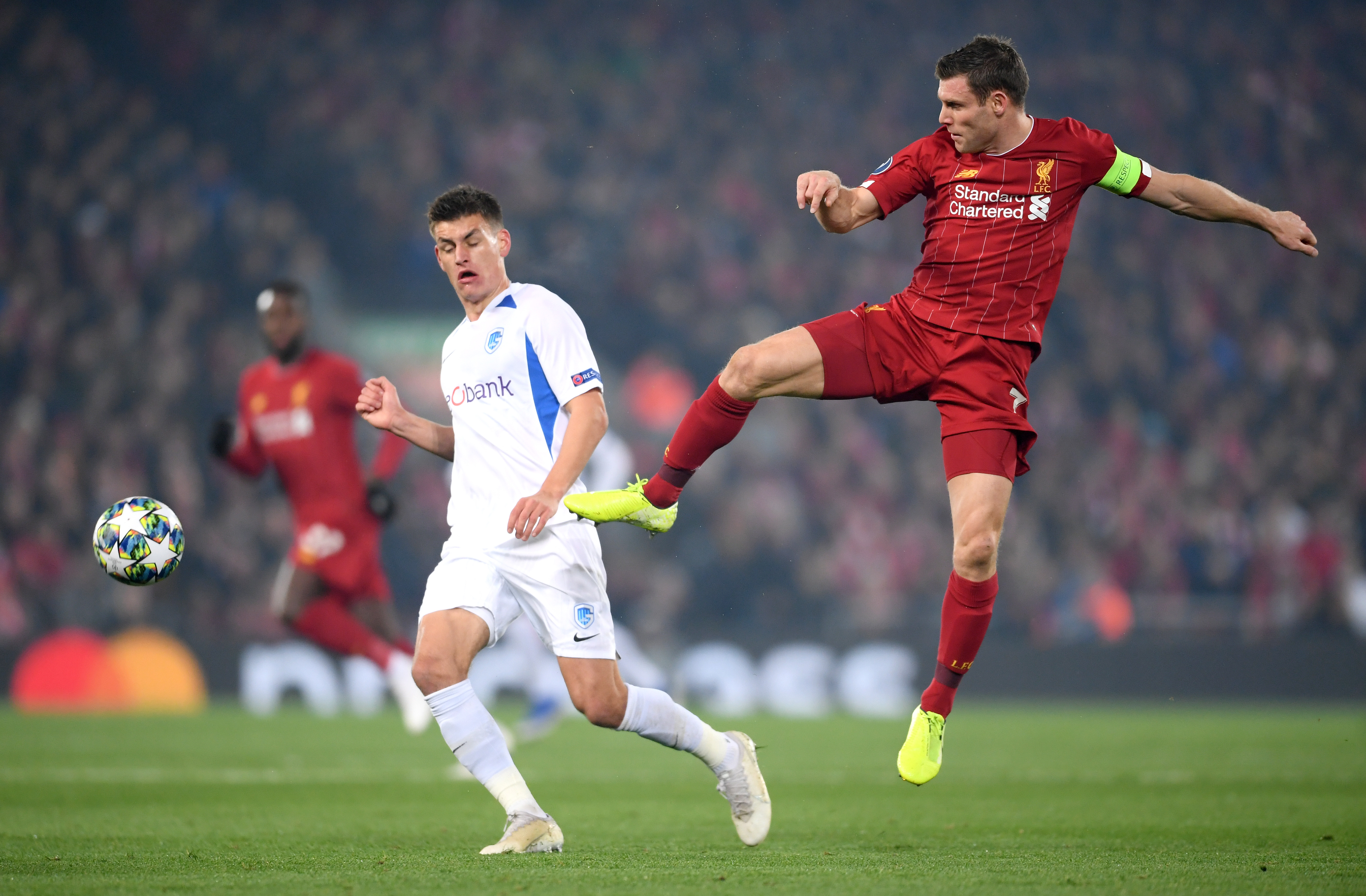 Joakim Maehle of KRC Genk battles for possession with James Milner of Liverpool.