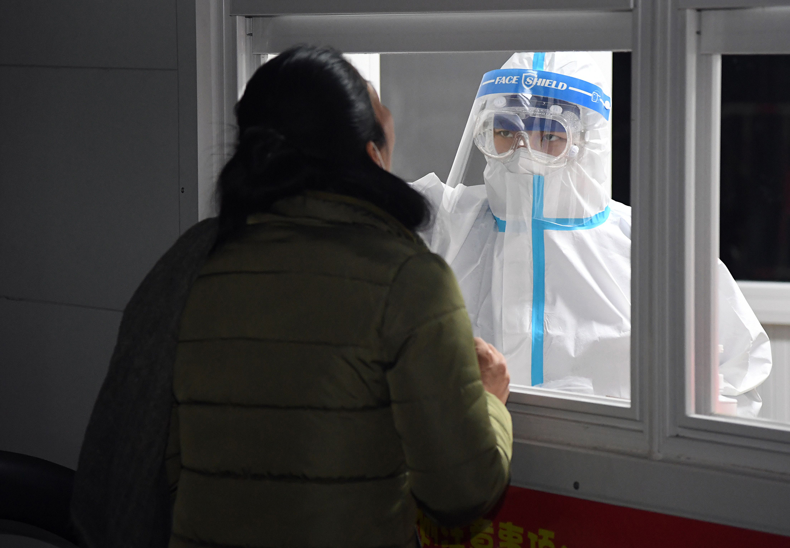 A medical worker collects sample to conduct a nucleic acid test at a sampling site in Shunyi District of Beijing, on December 26.