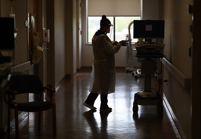A member of the dialysis team dons personal protective equipment (PPE) before treating a patient with coronavirus in the intensive care unit at a hospital on May 1, 2020 in Leonardtown, Maryland.