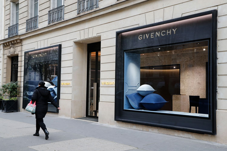 A pedestrian walks past a Givenchy shop closed due to the spread of the coronavirus on March 16 in Paris.