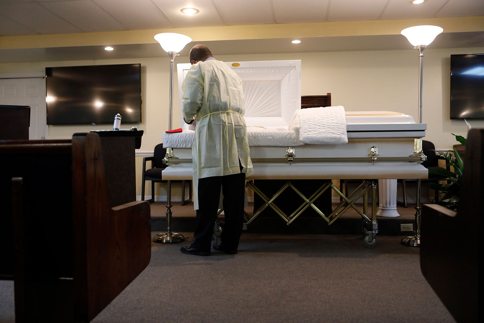 Funeral home director Jeffrey Rhodes prepares the body of man who died from coronavirus in Tampa, Florida.