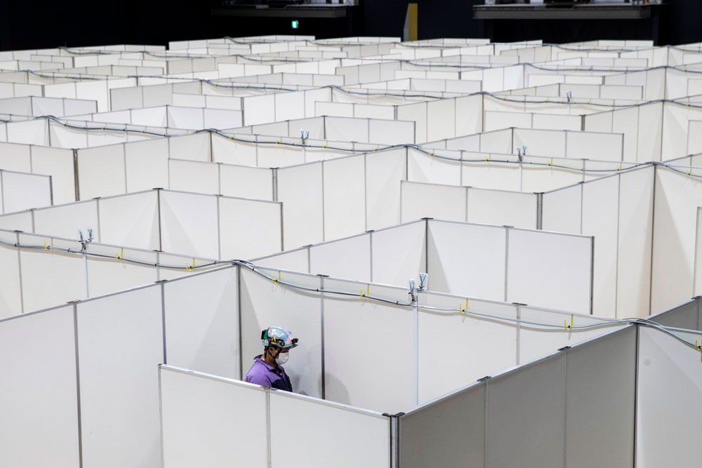 An employee helps set up a medical facility to accommodate coronavirus patients at the Nippon Foundation Para Arena in Tokyo on May 4.