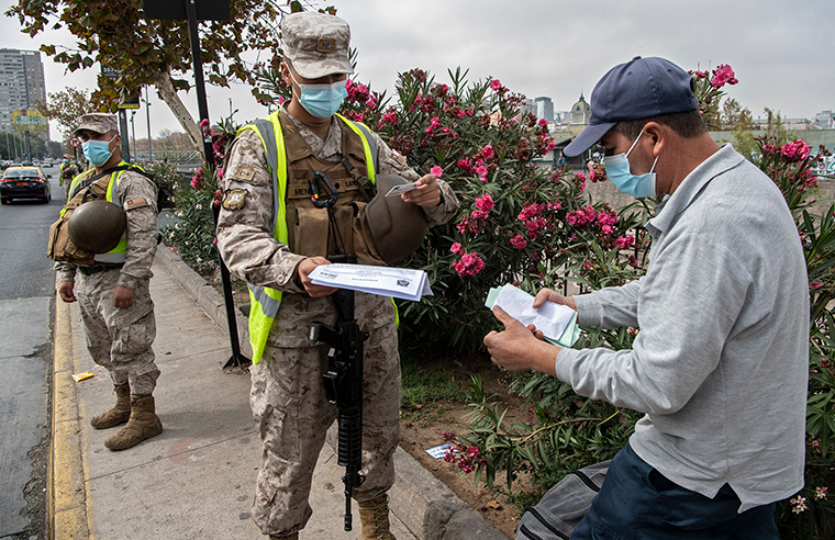 A soldier checks a pedestrian's ID at a checkpoint in Santiago, on March 25, as a new quarantine began Chile, due to a sharp increase in new cases of covid-19.
