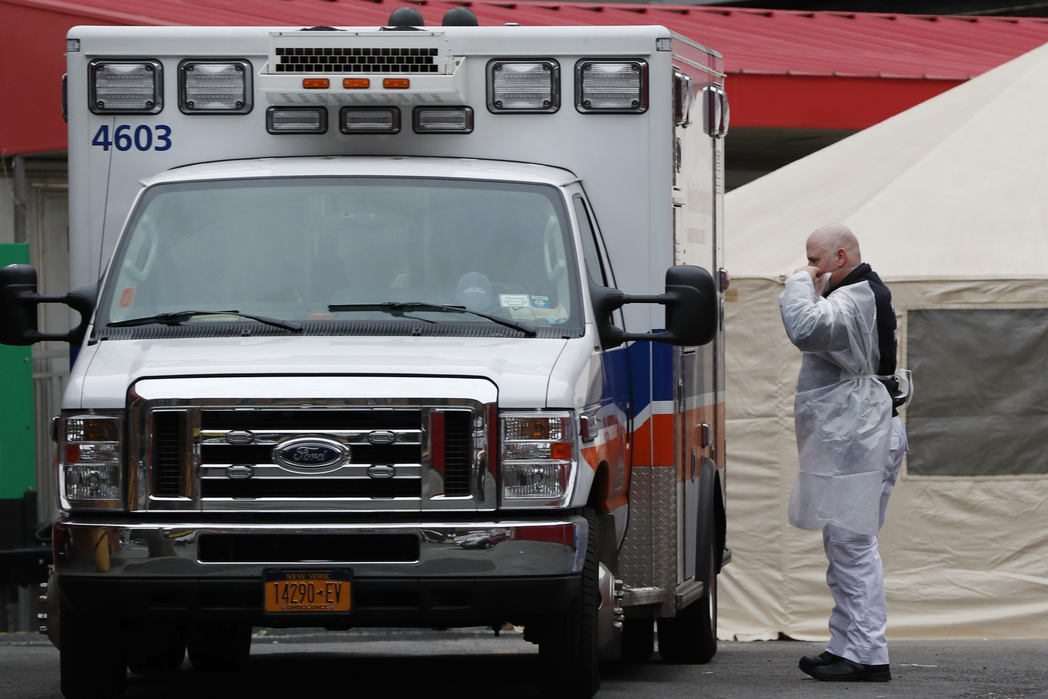An ambulance attendant adjusts his face mask before transferring a patient to the emergency department of Elmhurst Hospital Center in New York on March 28.