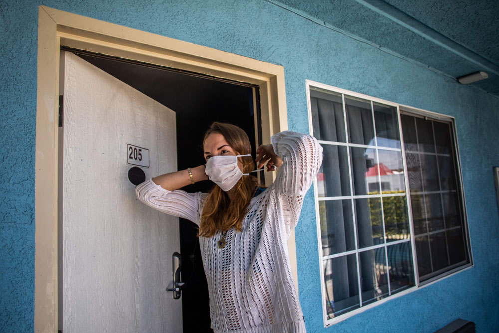 "A homeless woman puts on her mask at a motel room provided to homeless people under the ""Project Roomkey"" program on April 26 in Venice Beach, California."