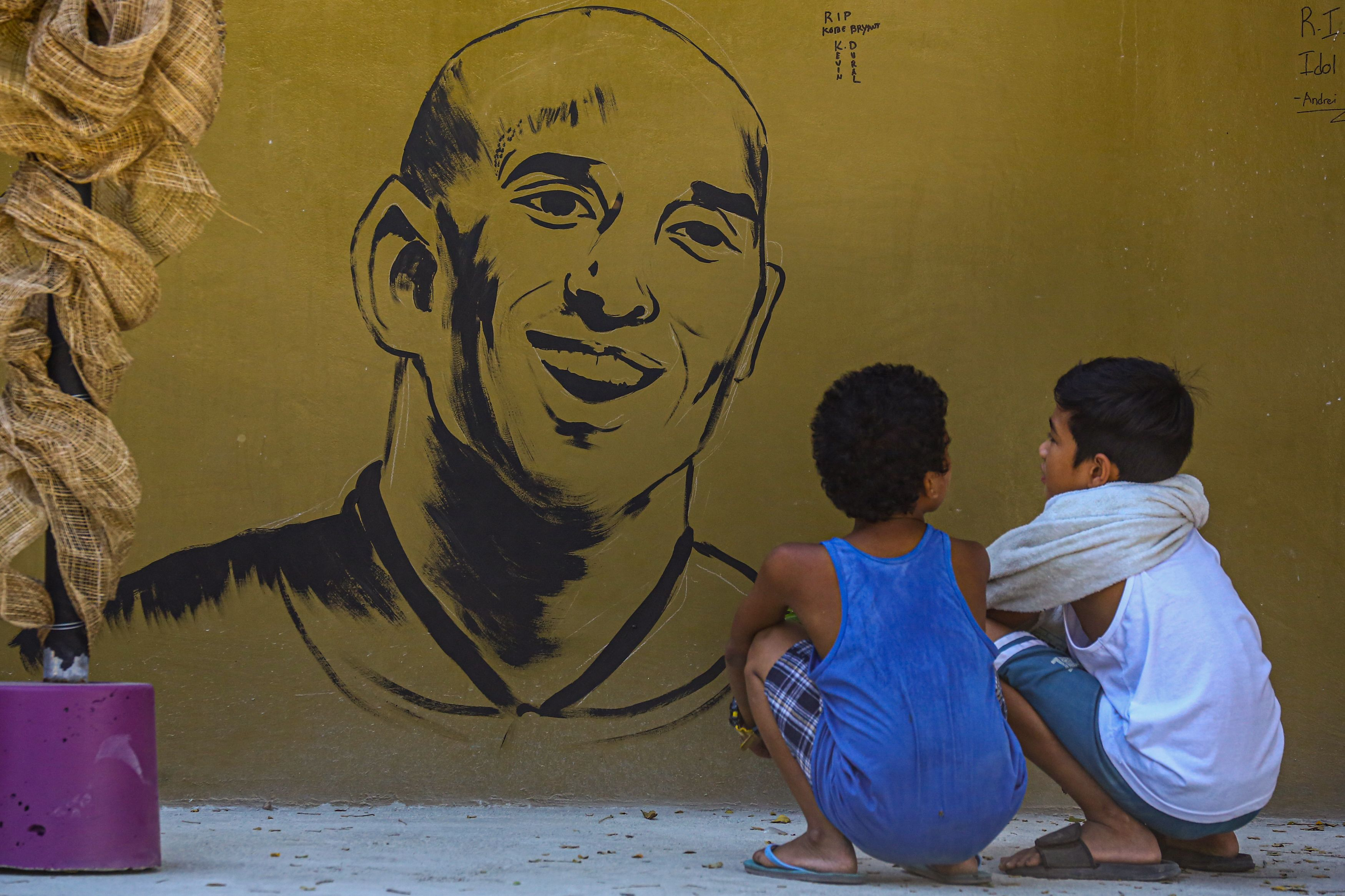 """Children look at a memorial wall for Bryant near the """"House of Kobe"""" gym built in honour of his 2016 visit to the Philippines, in Manila."""