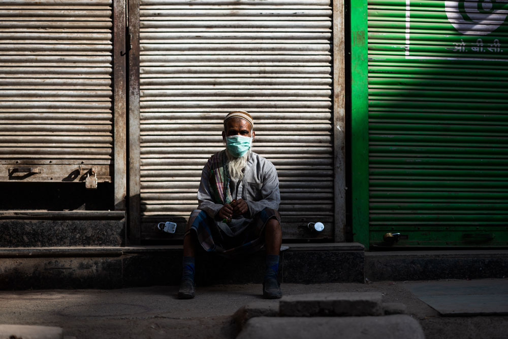 A man wearing a face mask sits in front of a closed shop during a government-imposed nationwide lockdown as a preventive measure against the coronavirus in New Delhi on April 6.