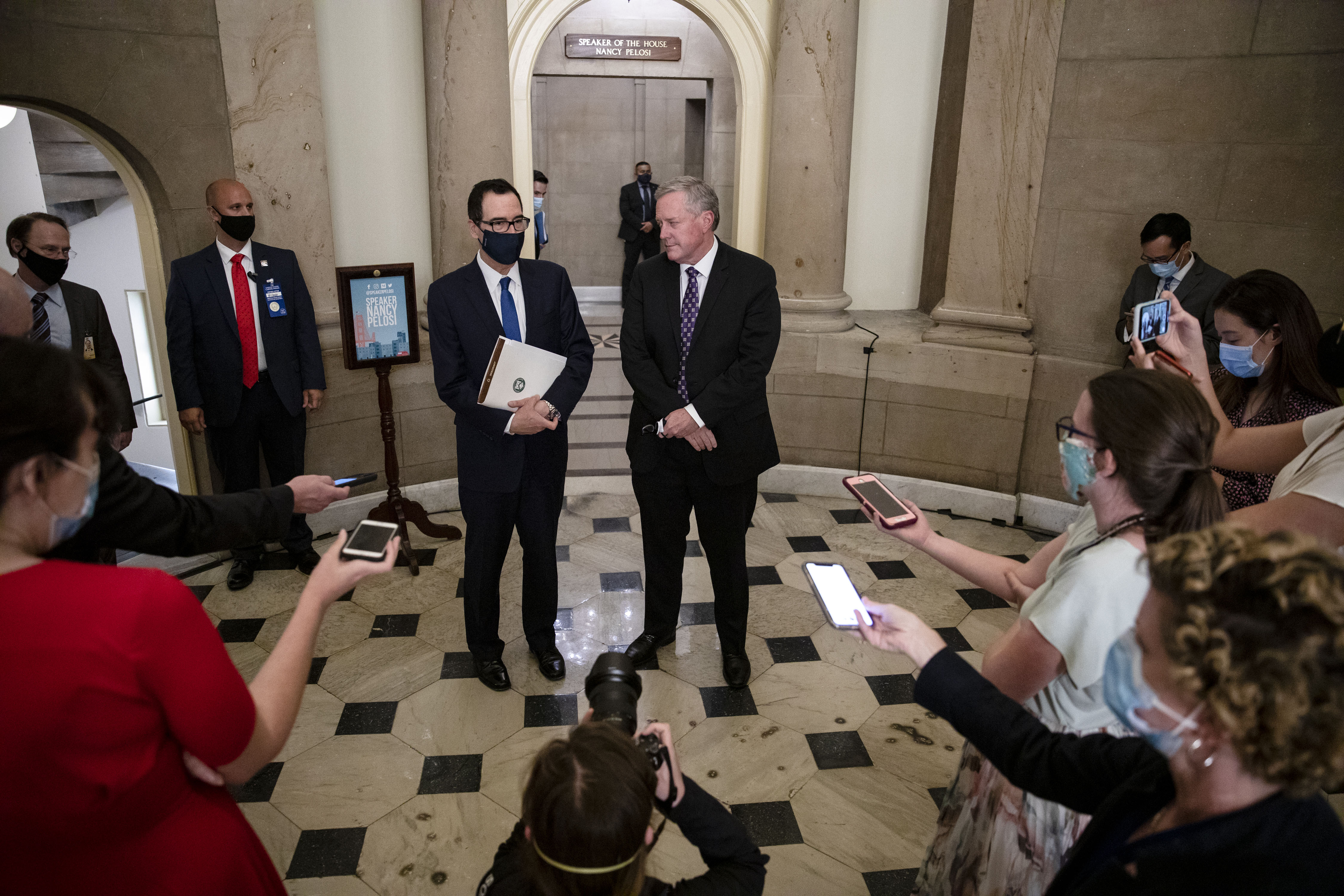 Treasury Secretary Steven Mnuchin and White House chief of staff Mark Meadows — center left and right, respectively — speak to reporters on July 30 in Washington, DC, after a meeting with Speaker Nancy Pelosi and Senate Democratic Leader Chuck Schumer.