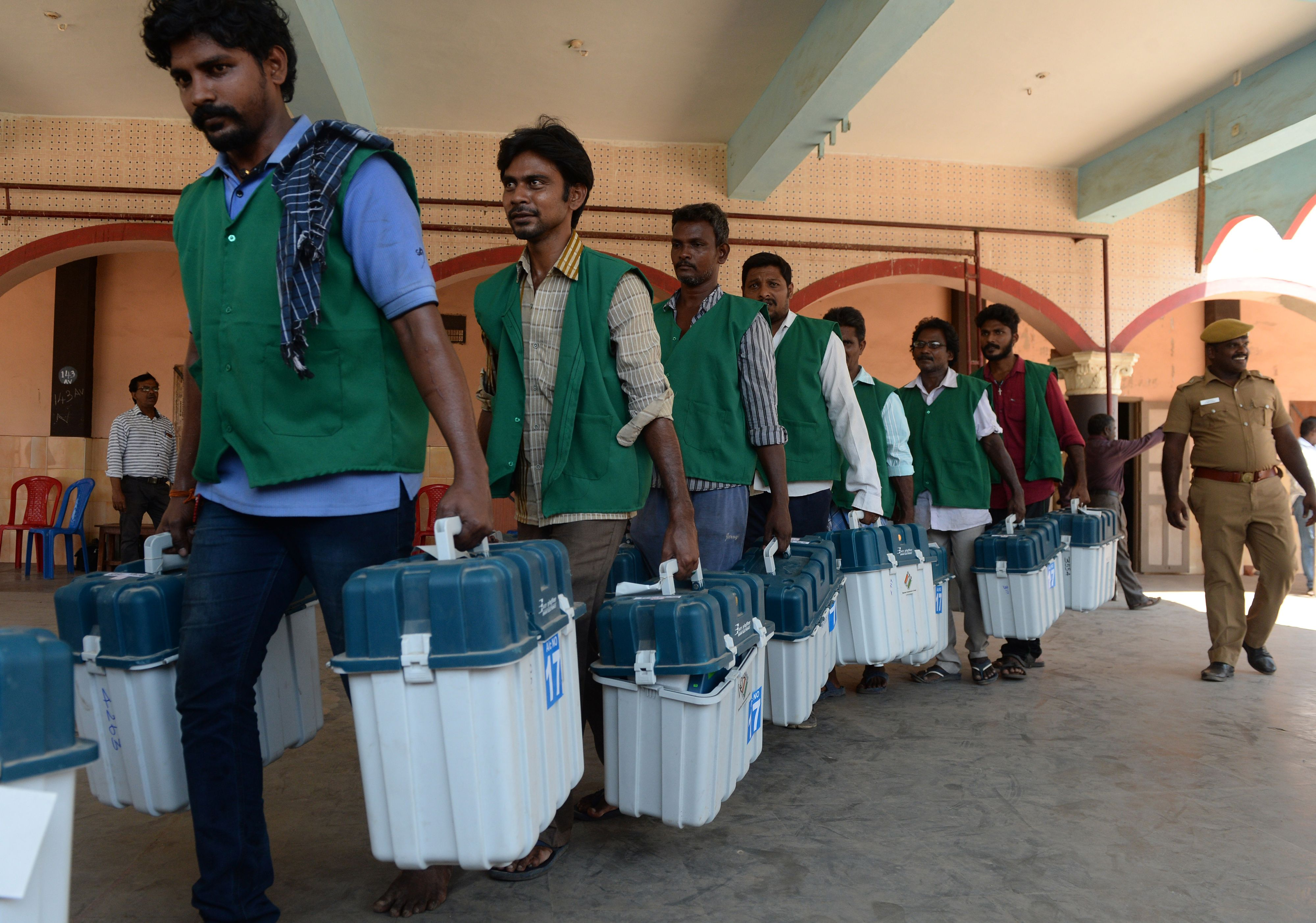 Indian election workers carry boxes containing Electronic Voting Machines at a distribution point in Chennai on April 17, 2019, ahead of the second phase of India's general election.