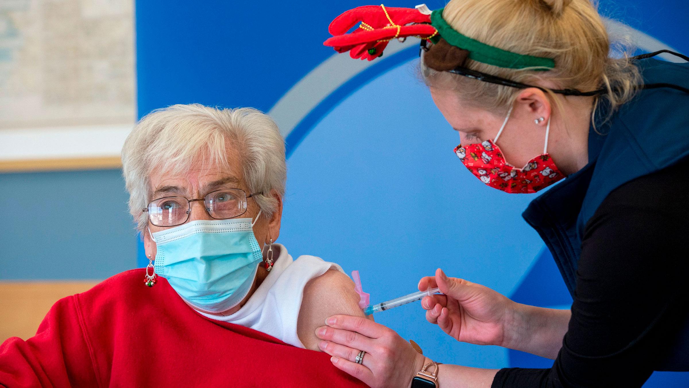 Nurse Courtney Senechal inoculates Phyllis Fischer with a Covid-19 vaccine in Boston.