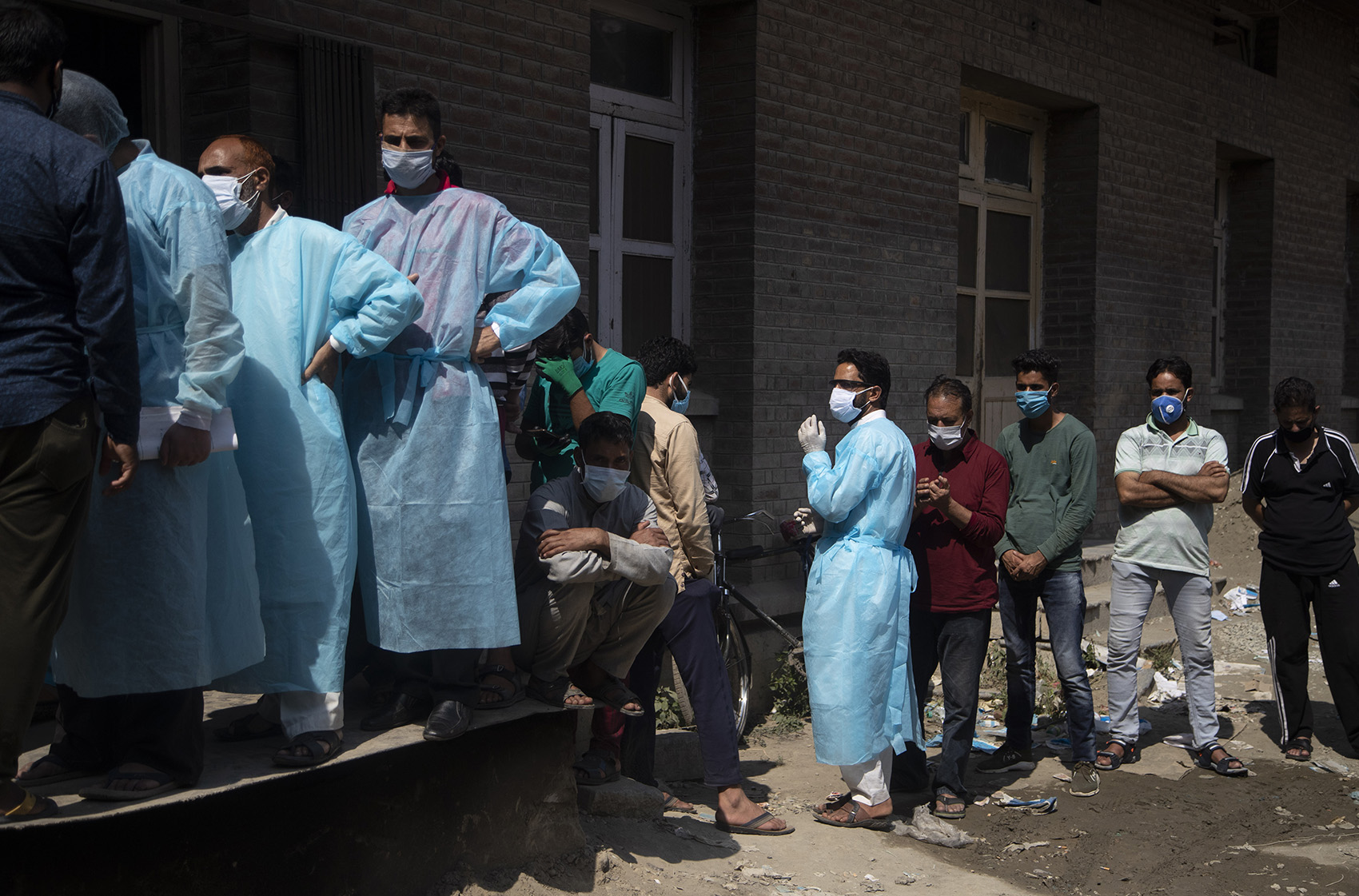 Relatives and bystanders, some of them wearing protective suits, line up to get oxygen cylinders for patients outside a hospital in Srinagar, Indian controlled Kashmir, on Wednesday, August 12.