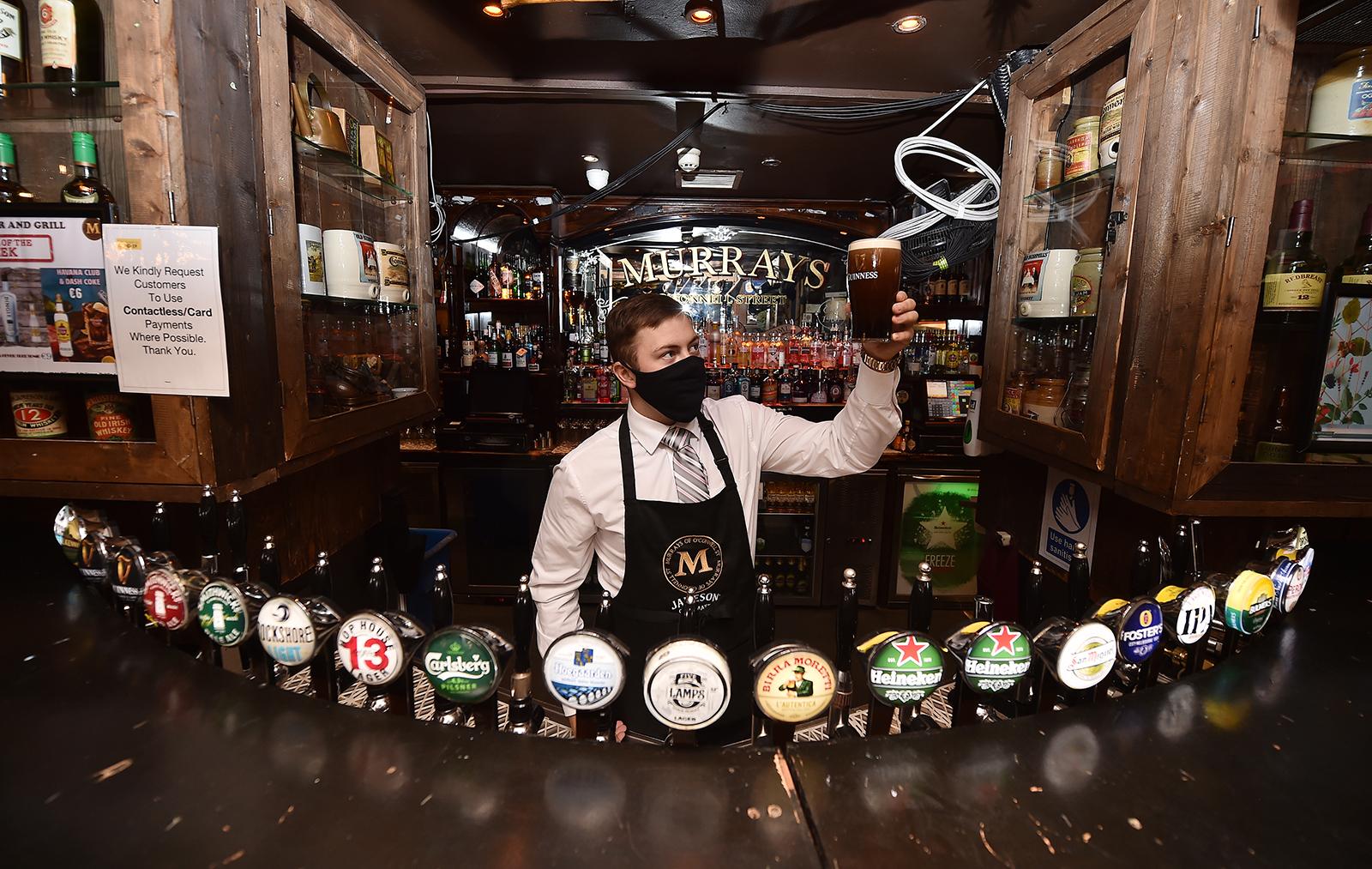 A barman in Murrays pub on Grafton street checks the head on a pint of Guinness on June 29 in Dublin, Ireland.